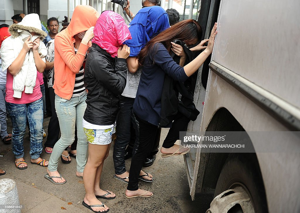 Arrested Chinese nationals board a police truck to be taken to a remand prison after being produced before the magistrate court in Colombo on December 22, 2012. Police in Sri Lanka on Saturday said had arrested 100 Chinese nationals for currency fraud in a string of raids in and around the capital Colombo in what they described as a case of cyber-crime.