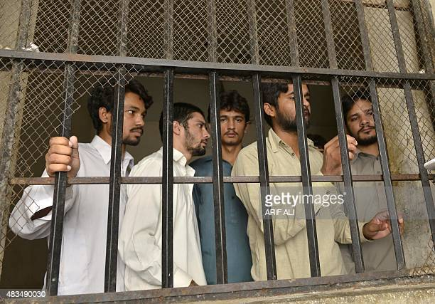 Arrested gang members of a sexual abuse scandal stand in the police lockup in Hussain Khanwala village some 55 kms southwest of Lahore on August 9...