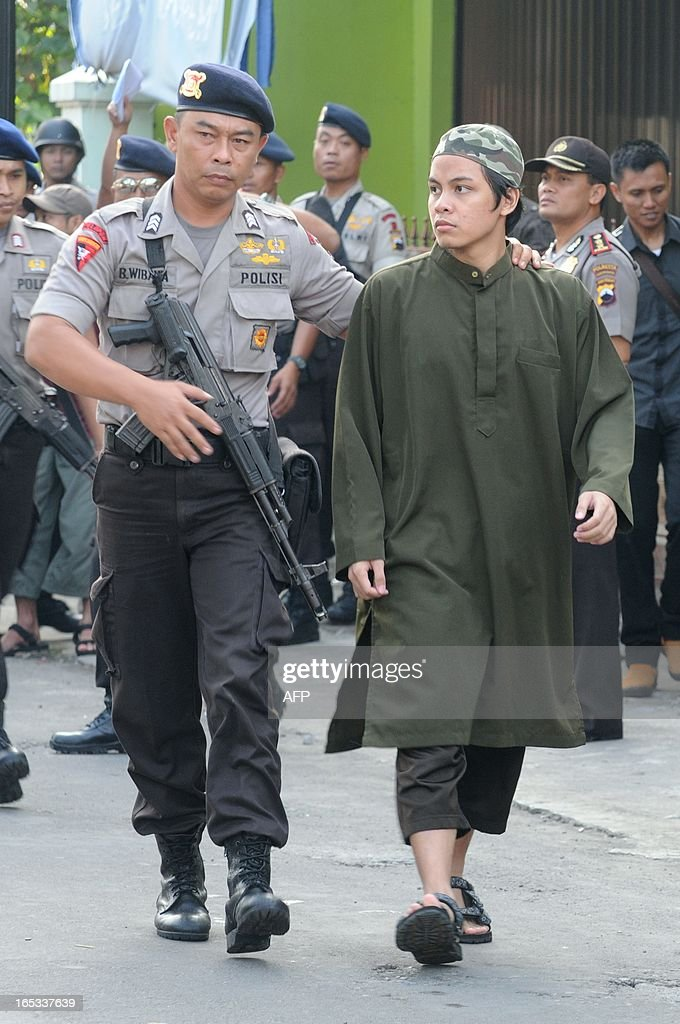 Arrested terror suspect Firman Firmansyah is escorted by armed police commandos in Solo city in central Java island on April 3, 2013 during the police reconstruction of the attacks on police outposts in the city on August 2012 where a policeman was shot and killed. According to the police the group's potential targets were the elite Brimob police headquarters, the office of Indonesia's counter terror Detachment 88 squad, and a police station in Jakarta. Indonesia, the biggest Muslim country by population, has waged a crackdown on militant groups over the past decade with anti-terror police claiming the deaths of some of the country's most notorious terrorist suspects in bloody raids.