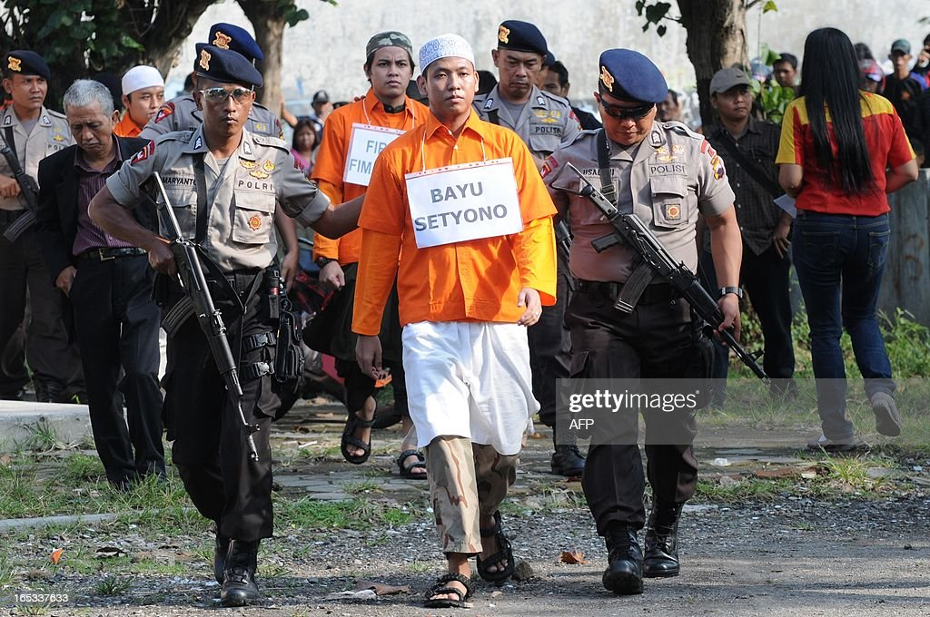 Arrested terror suspects Bayu Setyono followed by Firman Firmansyah are escorted by armed police commandos in Solo city in central Java island on April 3, 2013 during the police reconstruction of the attacks on police outposts in the city on August 2012 where a policeman was shot and killed. According to the police the group's potential targets were the elite Brimob police headquarters, the office of Indonesia's counter terror Detachment 88 squad, and a police station in Jakarta. Indonesia, the biggest Muslim country by population, has waged a crackdown on militant groups over the past decade with anti-terror police claiming the deaths of some of the country's most notorious terrorist suspects in bloody raids. AFP PHOTO / ANWAR MUSTAFA