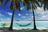 A cruise ship appears on the horizon of a tropical turquoise lagoon - with a hammock in semi silhouette, shaded by palm trees