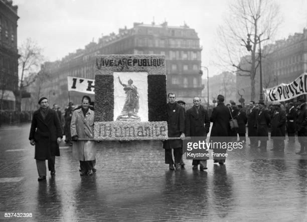 Arrivée des anciens prisonniers de guerre portant une stèle de fleurs du journal l'Humanité à l'effigie de Marianne où il est écrit 'Vive la...