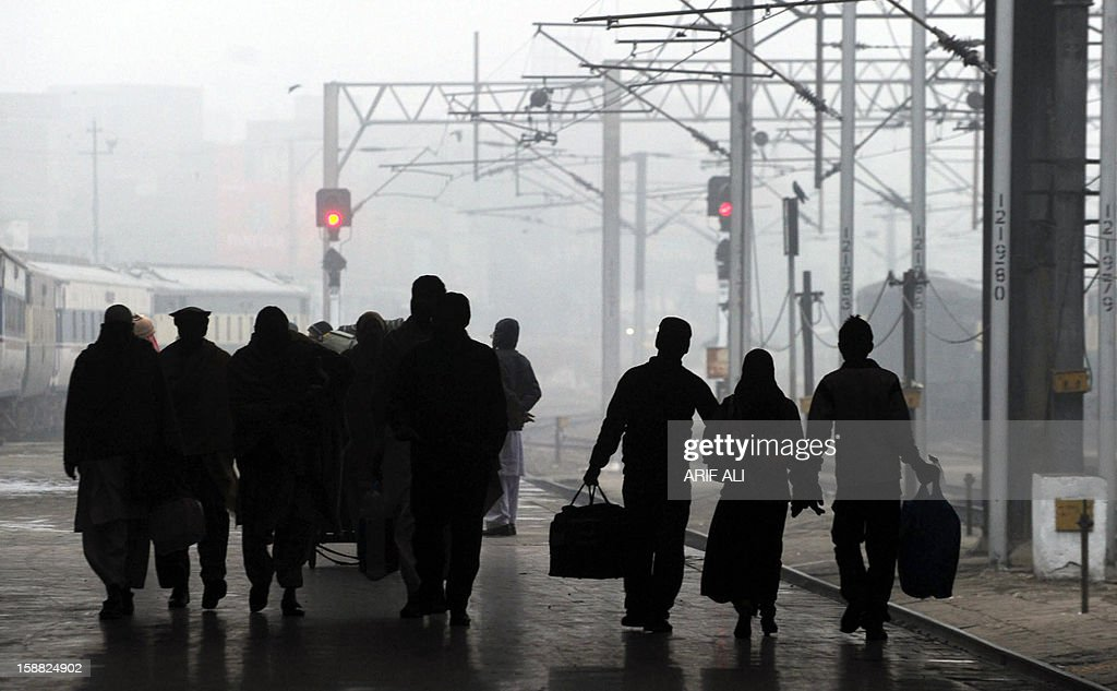Arriving passengers walk on the platform during a cold and foggy morning at a railway station in Lahore on December 31, 2012. Ongoing foggy weather in Punjab and other parts of the country has badly affected flight and rail schedules. AFP PHOTO/ARIF ALI