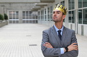 Arrogant businessman with a crown in office space.