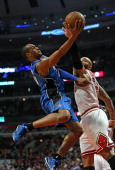 Arron Afflalo of the Orlando Magic puts up a shot against Carlos Boozer of the Chicago Bulls at the United Center on December 16 2013 in Chicago...