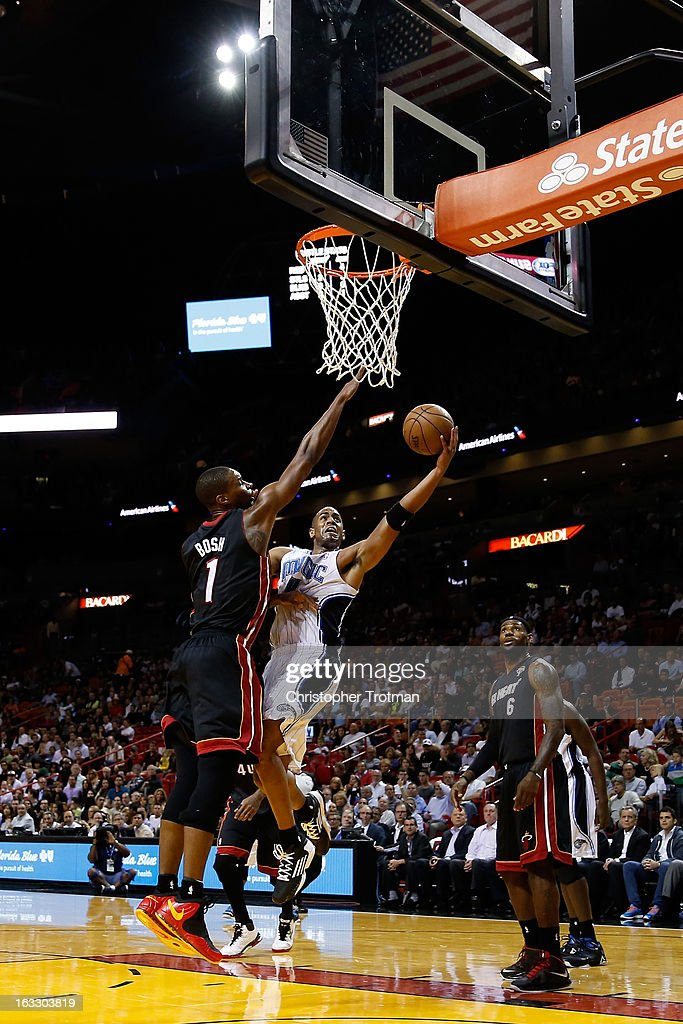 Arron Afflalo #4 of the Orlando Magic shoots past Chris Bosh #1 of the Miami Heat at American Airlines Arena on March 6, 2013 in Miami, Florida.