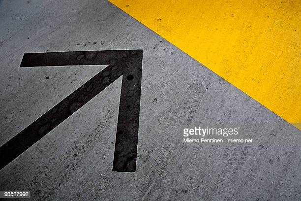 Arrow, a yellow wedge and tire marks on pavement