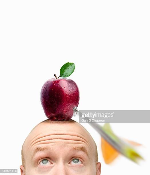 Arrow flying toward apple on bald man's head