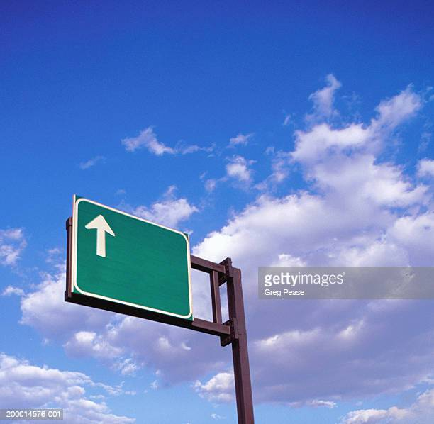 Arrow highway road sign against cloudy sky