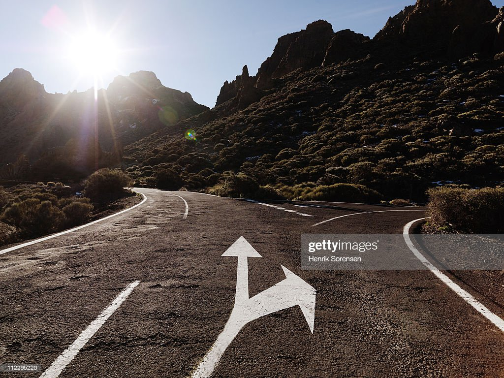 Arrow indicating side road in mountain landscape : Stock Photo