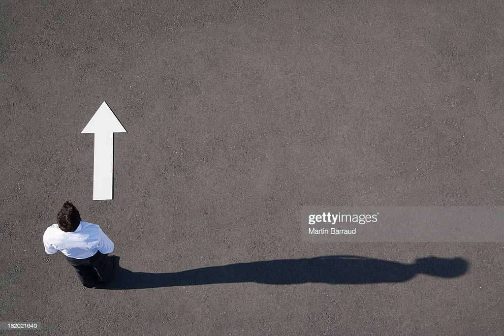 Arrow on pavement pointing away from businessman