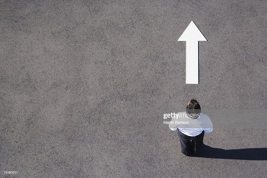 Arrow on pavement pointing away from businessman : Stock Photo