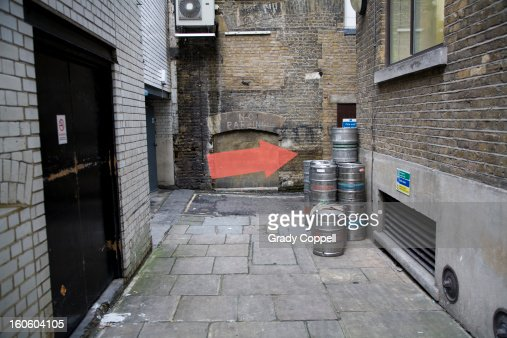 Arrow pointing way down an alleyway : Stock Photo