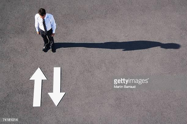 上を指す矢印の舗装から離れているビジネスマン