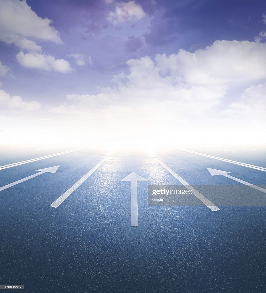 Arrows pointing into bright light : Stock Photo