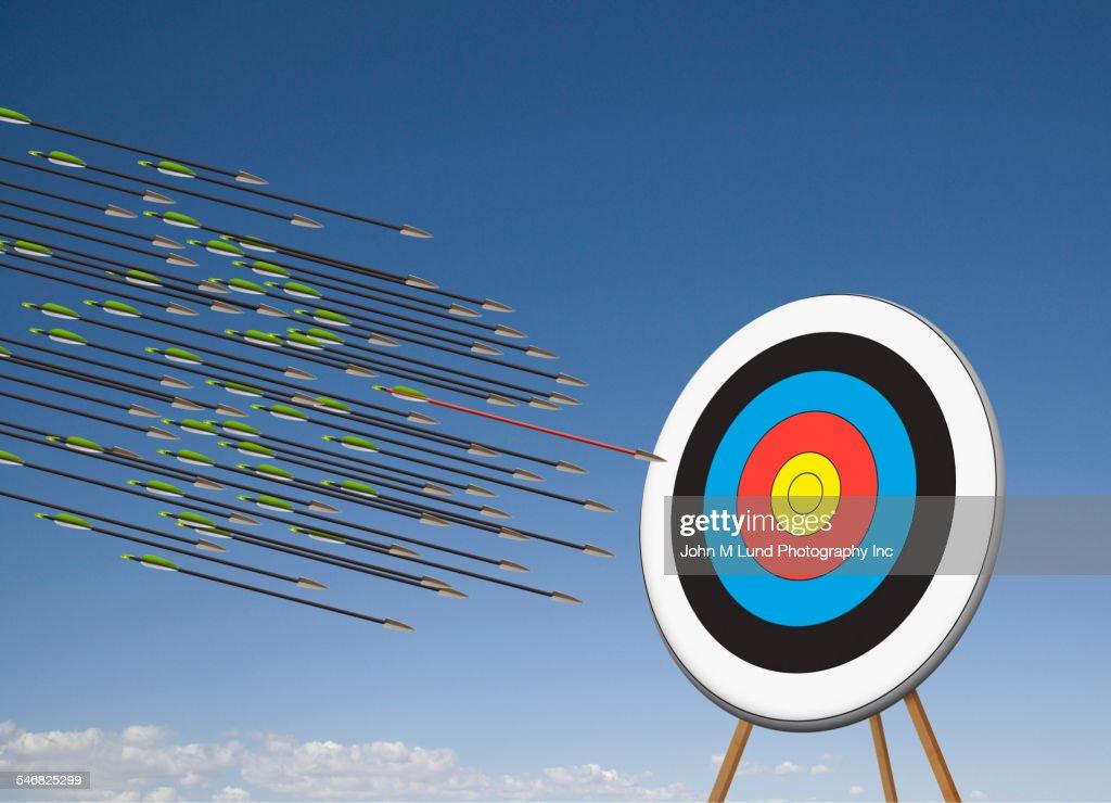 Arrows shooting towards target in blue sky