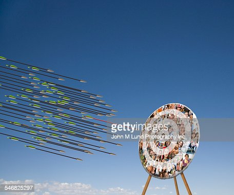 Arrows shooting towards target with faces in blue sky