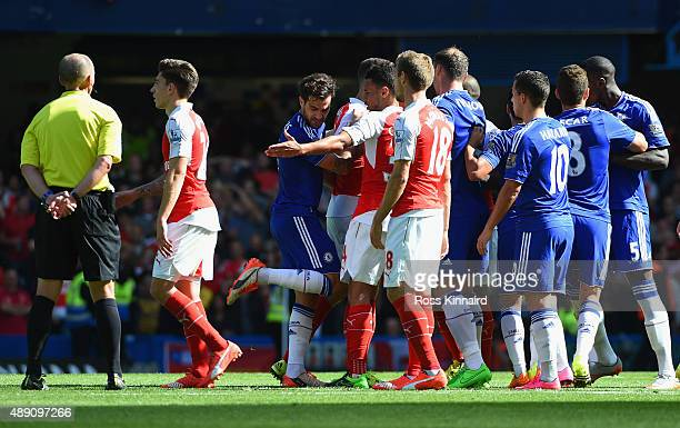Arsenal and Chelsea players face off while referee Mike Dean watches during the Barclays Premier League match between Chelsea and Arsenal at Stamford...