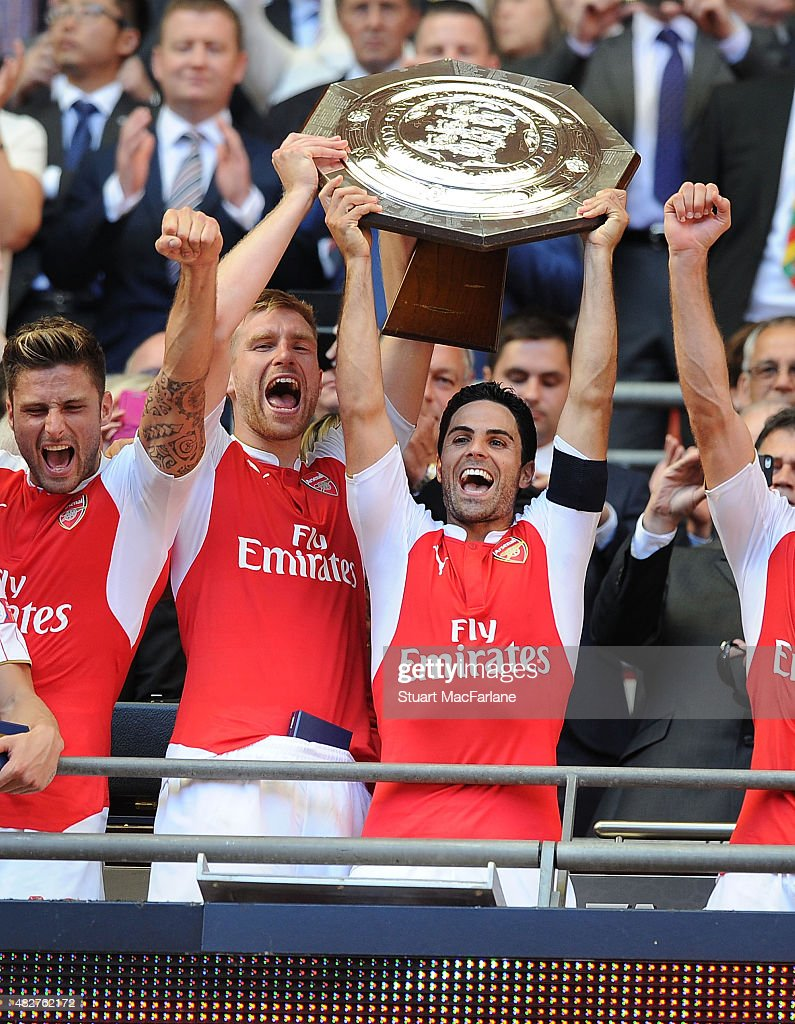 Arsenal captain Mike Arteta and (L) vice captain Per Mertesacker lift the Community shield after the FA Community Shield match between Chelsea and Arsenal at Wembley Stadium on August 2, 2015 in London, England.