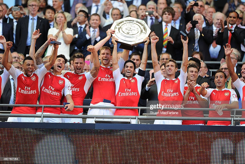 Arsenal captain Mikel Arteta lifts the Community Shield with (4thL) vice captain Per Mertesacker after the FA Community Shield match between Chelsea and Arsenal at Wembley Stadium on August 2, 2015 in London, England.