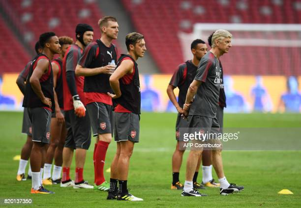 Arsenal coach Arsene Wenger stands with players during a football training session in Beijing's National Stadium known as the Bird's Nest on July 21...