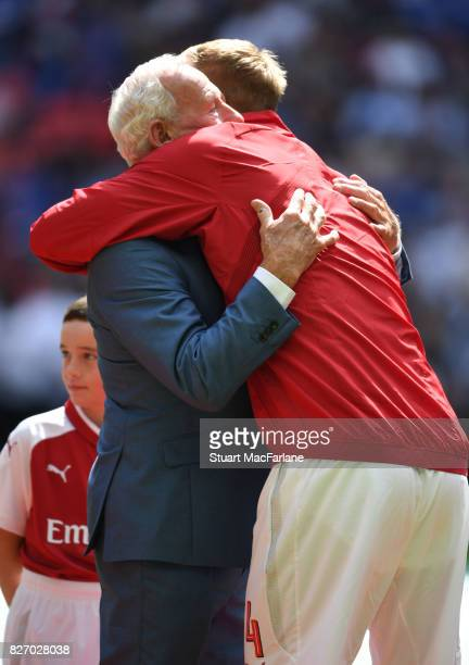 Arsenal cpatain Per Mertesacker hugs former player Bob Wilson before the FA Community Shield match between Chelsea and Arsenal at Wembley Stadium on...