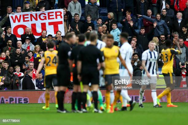 Arsenal fans display banners during the Premier League match between West Bromwich Albion and Arsenal at The Hawthorns on March 18 2017 in West...
