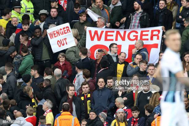 Arsenal fans display Wenger out banners during the Premier League match between West Bromwich Albion and Arsenal at The Hawthorns on March 18 2017 in...