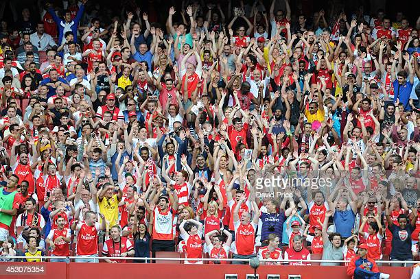Arsenal fans do a mexican wave during the Emirates Cup match between Arsenal and Benfica at Emirates Stadium on August 2 2014 in London England