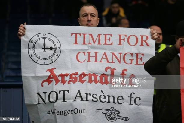 Arsenal fans hold up anti Arsene Wenger signs after the English Premier League football match between West Bromwich Albion and Arsenal at The...