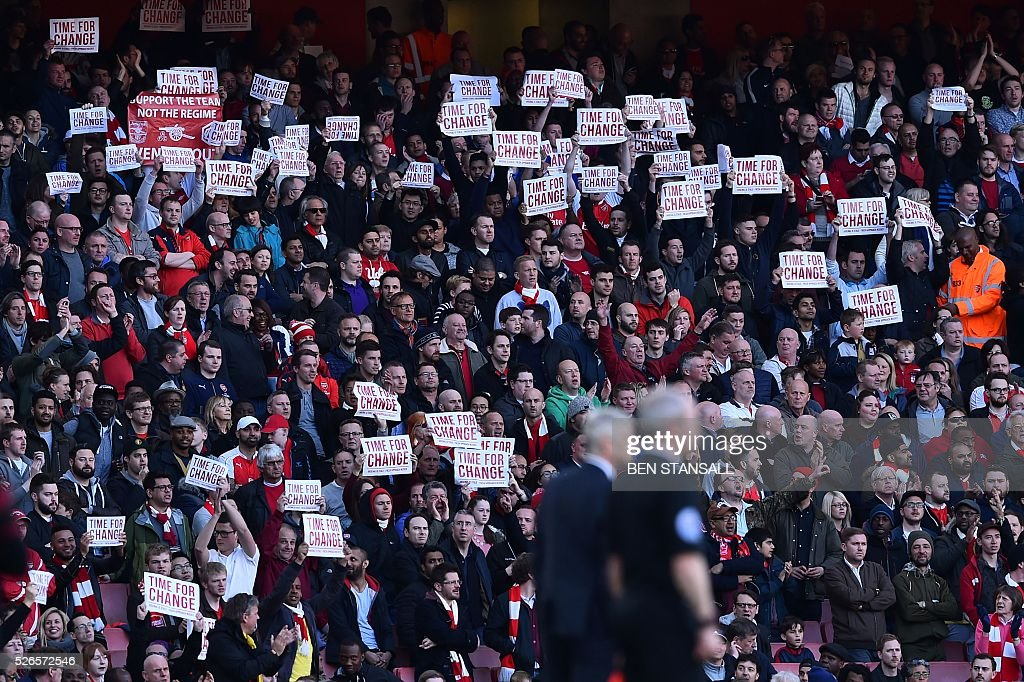 Arsenal fans hold up signs calling for change at the football club during the English Premier League football match between Arsenal and Norwich at the Emirates Stadium in London on April 30, 2016. / AFP / Ben STANSALL / RESTRICTED TO EDITORIAL USE. No use with unauthorized audio, video, data, fixture lists, club/league logos or 'live' services. Online in-match use limited to 75 images, no video emulation. No use in betting, games or single club/league/player publications. /