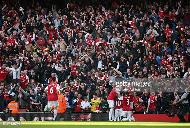 Arsenal fans / supporters celebrate as Robin van Persie of Arsenal celebrates scoring to make it 22 in front of them