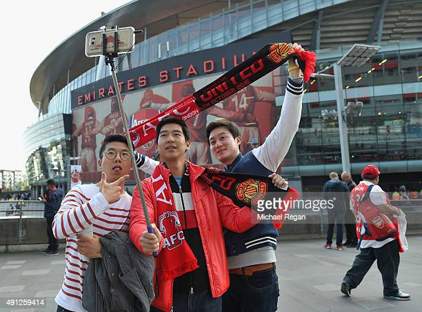 Arsenal fans take a selfie ahead the Barclays Premier League match between Arsenal and Manchester United at Emirates Stadium on October 4 2015 in...