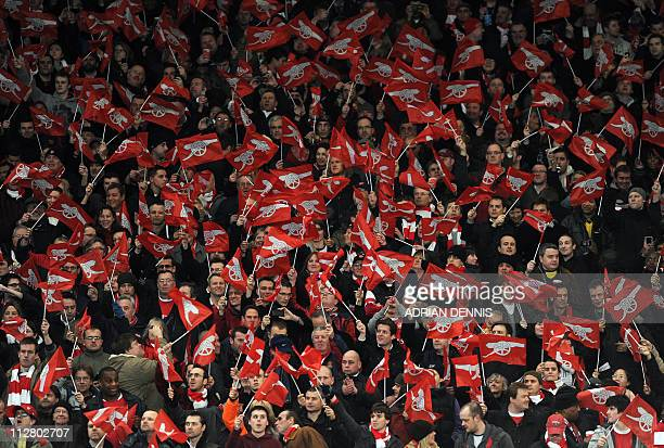 Arsenal fans wave flags before their UEFA Champions League round of 16 1st leg football match against Barcelona at the Emirates Stadium London...