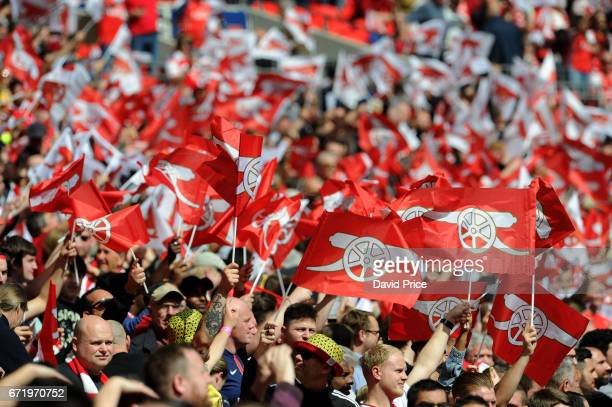 Arsenal fans wave their flags before the match between Arsenal and Manchester City at Wembley Stadium on April 23 2017 in London England