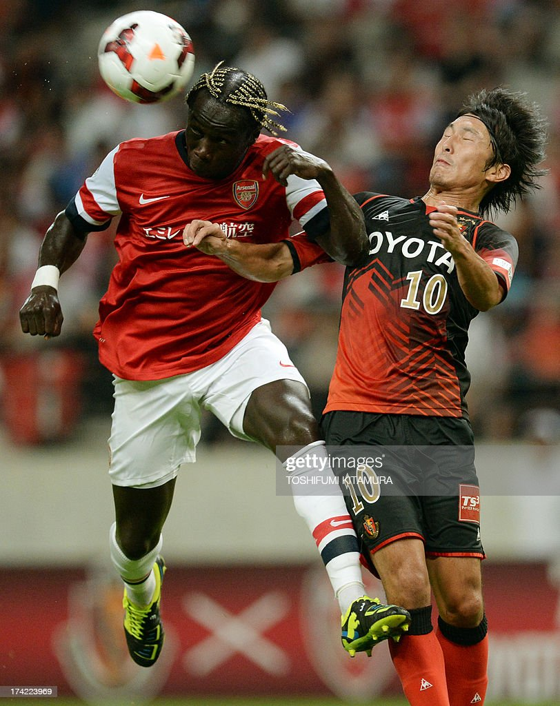 Arsenal FC defender Bacary Sagna (L) clears the ball beside Nagoya Grampus midfielder Yoshizumi Ogawa (R) during their friendly match in Toyota, Aichi prefecture on July 22, 2013.