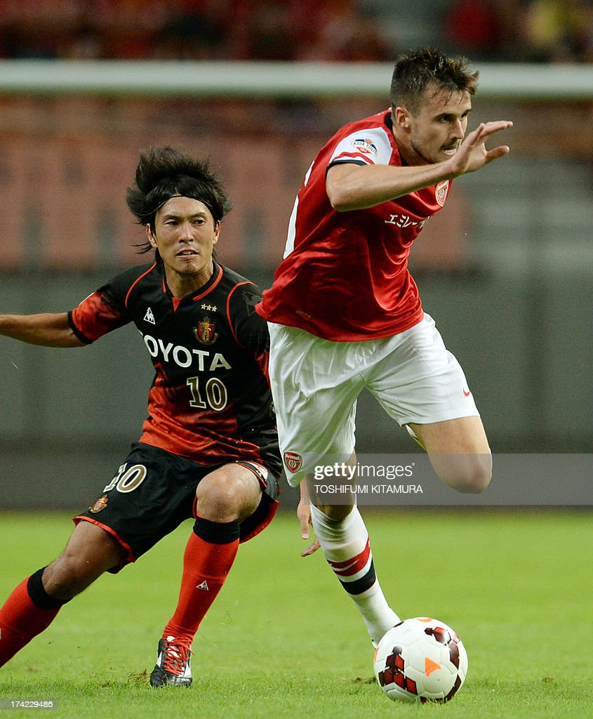 Arsenal FC defender Carl Jenkinson (R) dribbles the ball past Nagoya Grampus midfielder Yoshizumi Ogawa during their friendly match in Toyota, Aichi prefecture on July 22, 2013.