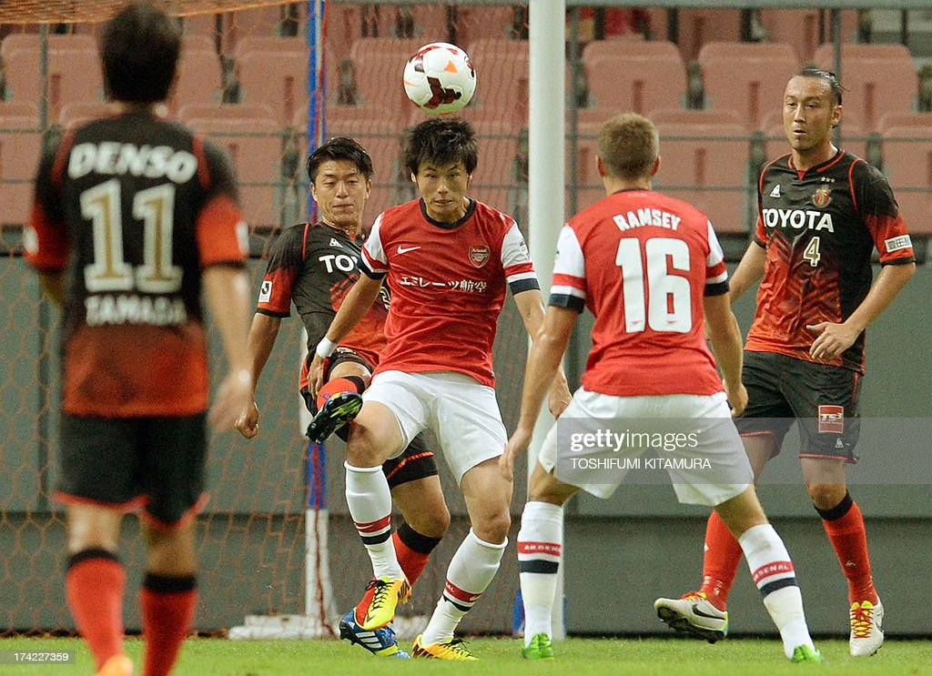 Arsenal FC forward Ryo Miyauchi (C) watches the ball in front of midfielder Aaron Ramsey (2nd R) during their friendly match against Nagoya Grampus in Toyota, Aichi prefecture on July 22, 2013.