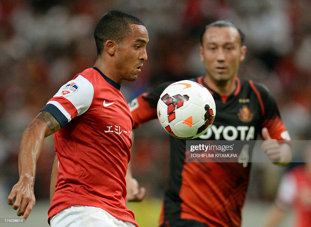 Arsenal FC forward Theo Walcott (L) traps the ball beside Nagoya Grampus defender Marcus Tulio Tanaka during their friendly match in Toyota, Aichi prefecture on July 22, 2013.
