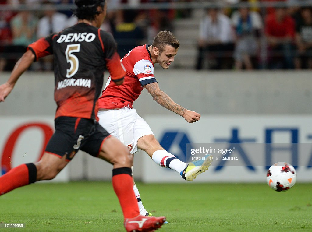 Arsenal FC midfielder Jack Wilshere (R) shoots the ball past Nagoya Grampus defender Takahiro Masukawa during their friendly match in Toyota, Aichi prefecture on July 22, 2013.
