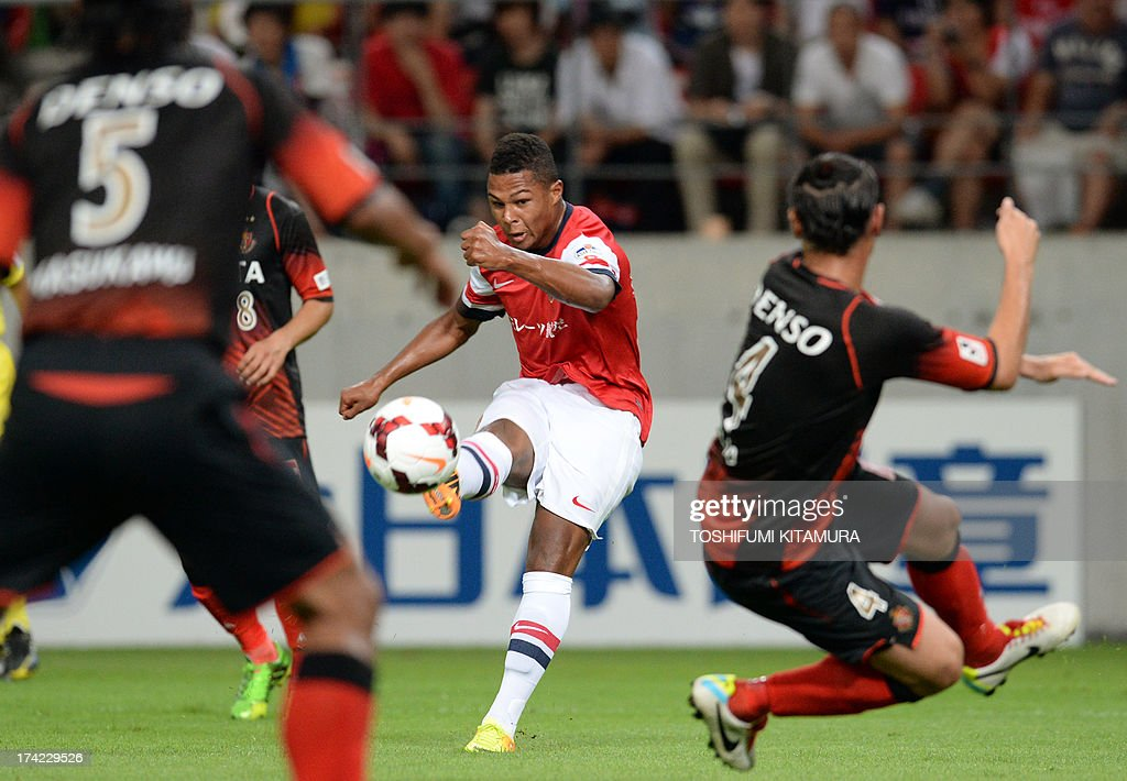 Arsenal FC midfielder Serge Gnabry (C) passes the ball through Nagoya Grampus defender Takahiro Masukawa (L) and defender Marcus Tulio Tanaka during their friendly match in Toyota, Aichi prefecture on July 22, 2013. AFP PHOTO / TOSHIFUMI KITAMURA