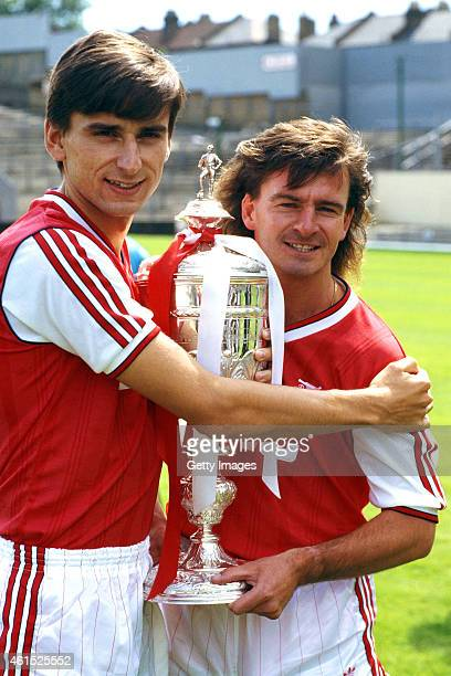 Arsenal forwards Alan Smith and Charlie Nicholas pictured with the previous seasons silverware the League Cup before the start of the 1987/88 season