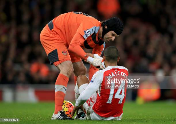Arsenal goalkeeper Petr Cech helps up teammate Theo Walcott after taking a knock