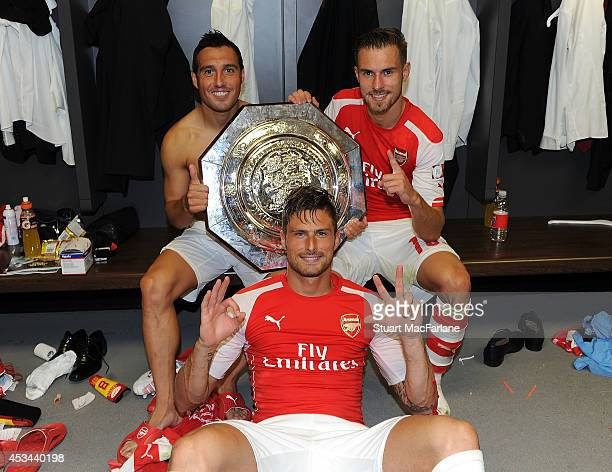 Arsenal goalscorers Santi Cazorla Olivier Giroud and Aaron Ramsey pose with the FA Community Shield after the FA Community Shield match between...