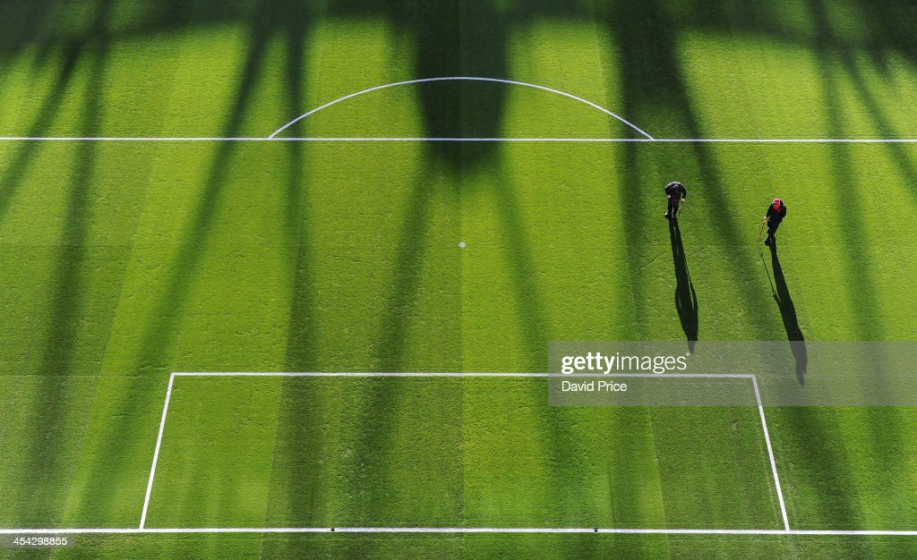 Arsenal groundsmen prepare the pitch before the Arsenal against Everton Premier League match at Emirates Stadium on December 8, 2013 in London, England.