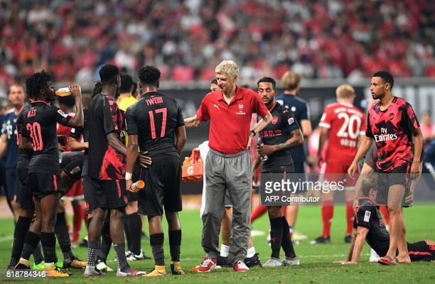 Arsenal head coach Arsene Wenger speaks to his players during the International Champions Cup football match between Bayern Munich and Arsenal in...
