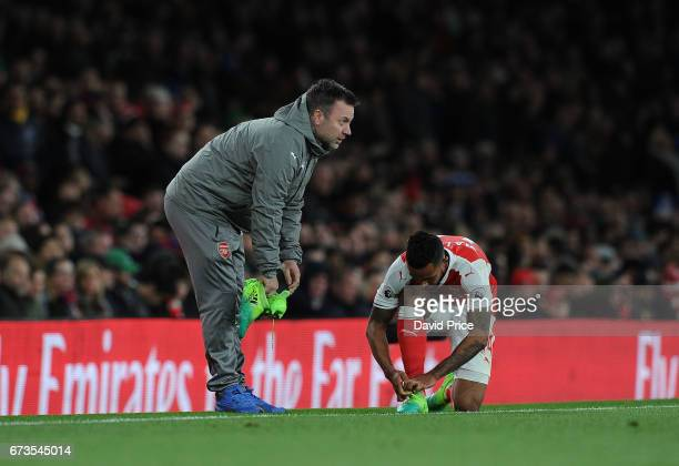 Arsenal kitman Paul Akers hands Theo Walcott of Arsenal new boots during the Premier League match between Arsenal and Leicester City at Emirates...