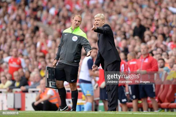 Arsenal manager Arsene Wenger argues with fourth official Robert Madley on the touchline during the Barclays Premier League match at The Emirates...