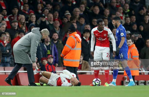 Arsenal manager Arsene Wenger attends to Alexis Sanchez during the Premier League match at the Emirates Stadium London