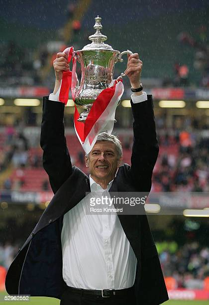 Arsenal Manager Arsene Wenger holds the trophy aloft after winning the FA Cup Final between Arsenal and Manchester United 54 on penalty's at The...